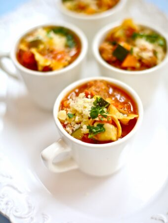 three cups of chicken sausage tortellini soup in white cups on white background on a white table
