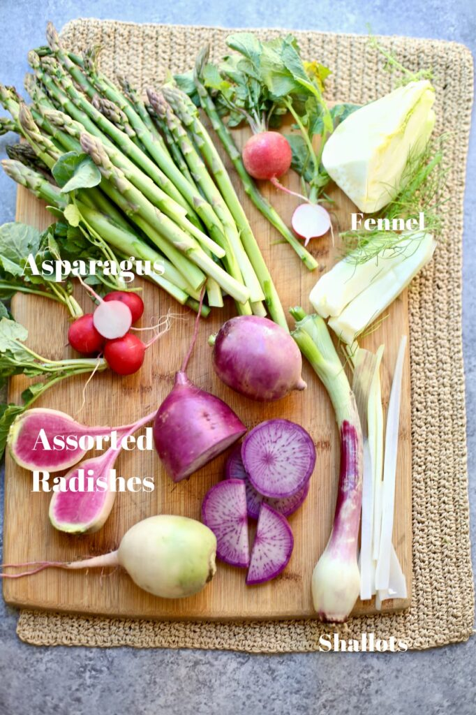 spring vegetables on a cutting board with text