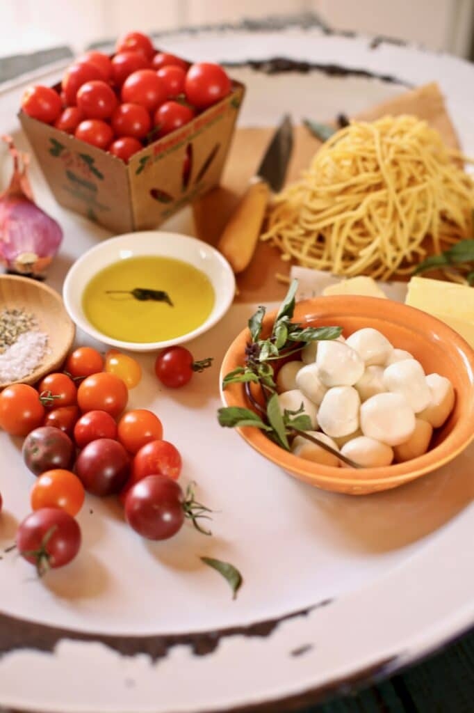 tomatoes and cheese and olivr oil and pasta on a table for spaghetti