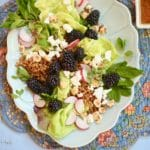 Blackberry Salad with Toasted Hazelnuts on a blue platter with a blue placemat underneath