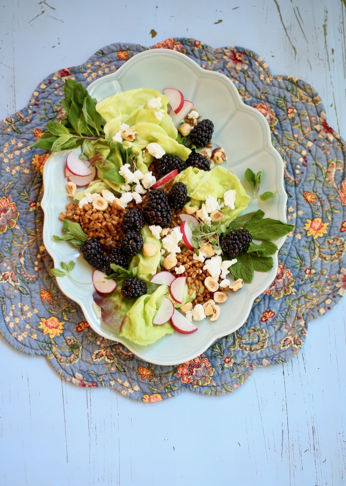 Long blue platter of salad made of goat cheese, blackberries, hazelnuts, radish and mint on a blue table