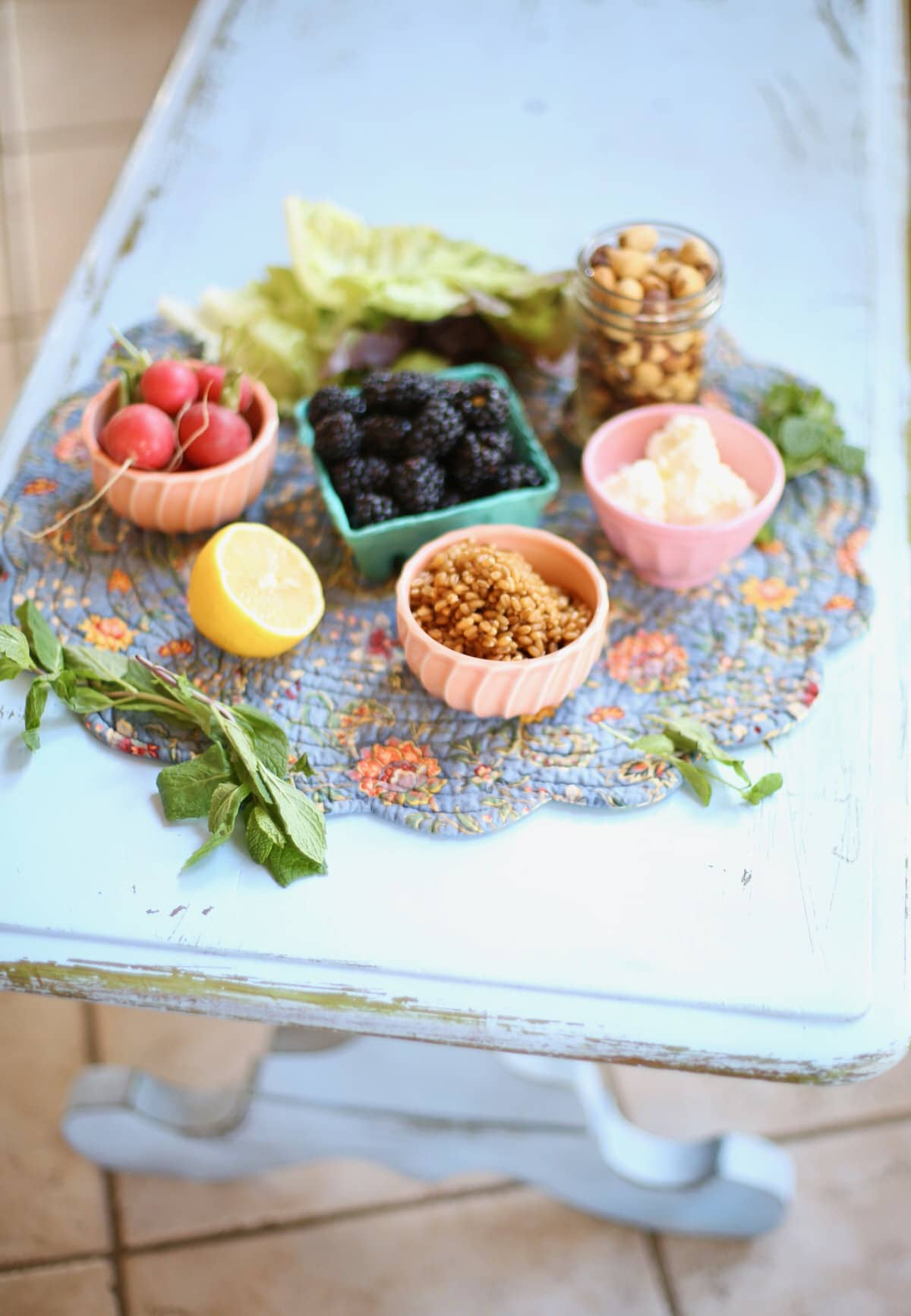 Ingredients for Blackberry Salad on a blue table: Grains, blackberries, hazelnuts, goat cheese, lemon, mint and radish in small bowls.