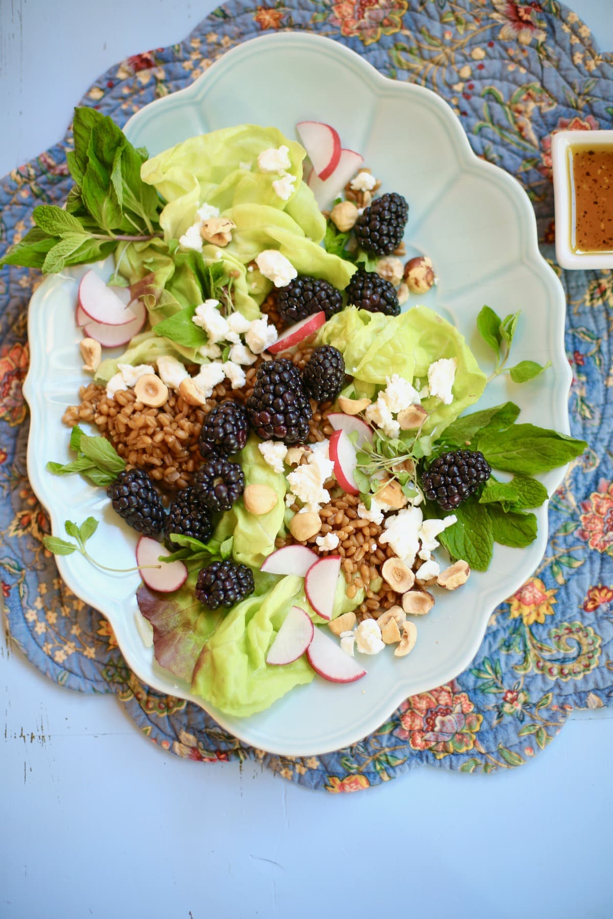 Salad with hazelnuts, greens, blackberries goat cheese grains and radish on a long blue plate on a table