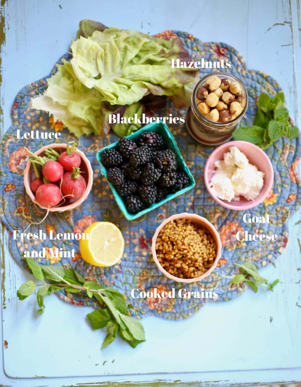 Ingredients for blackberry salad with white text overlay on a blue fabric place mat.