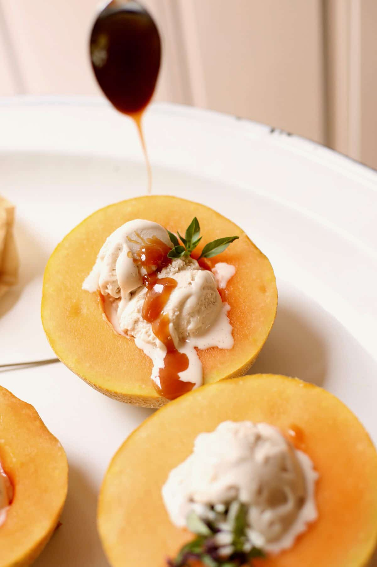 melon with ice cream and caramel sauce being poured over the top