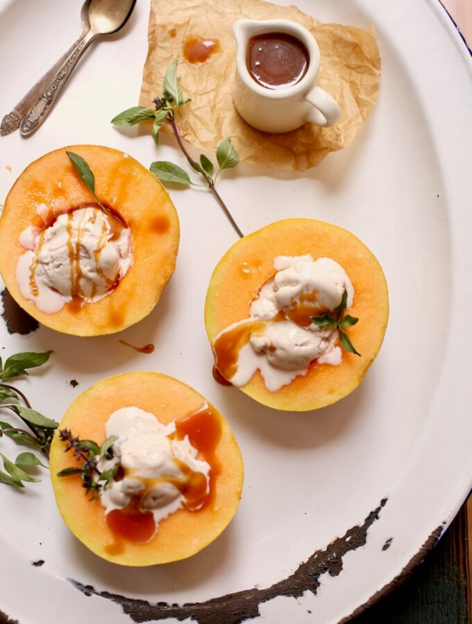three melons and ice cream on a white platter