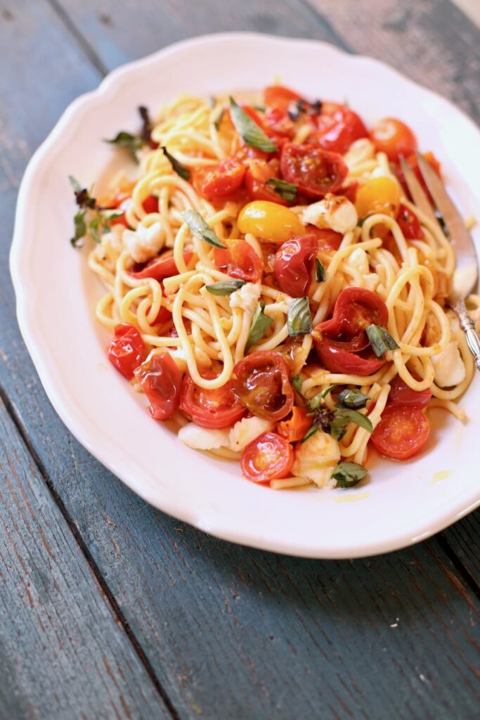 Pasta with tomatoes on a white plate and blue table