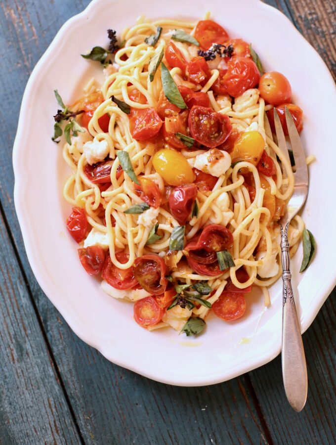 pasta with tomatoes on a white plate and blue wooden table