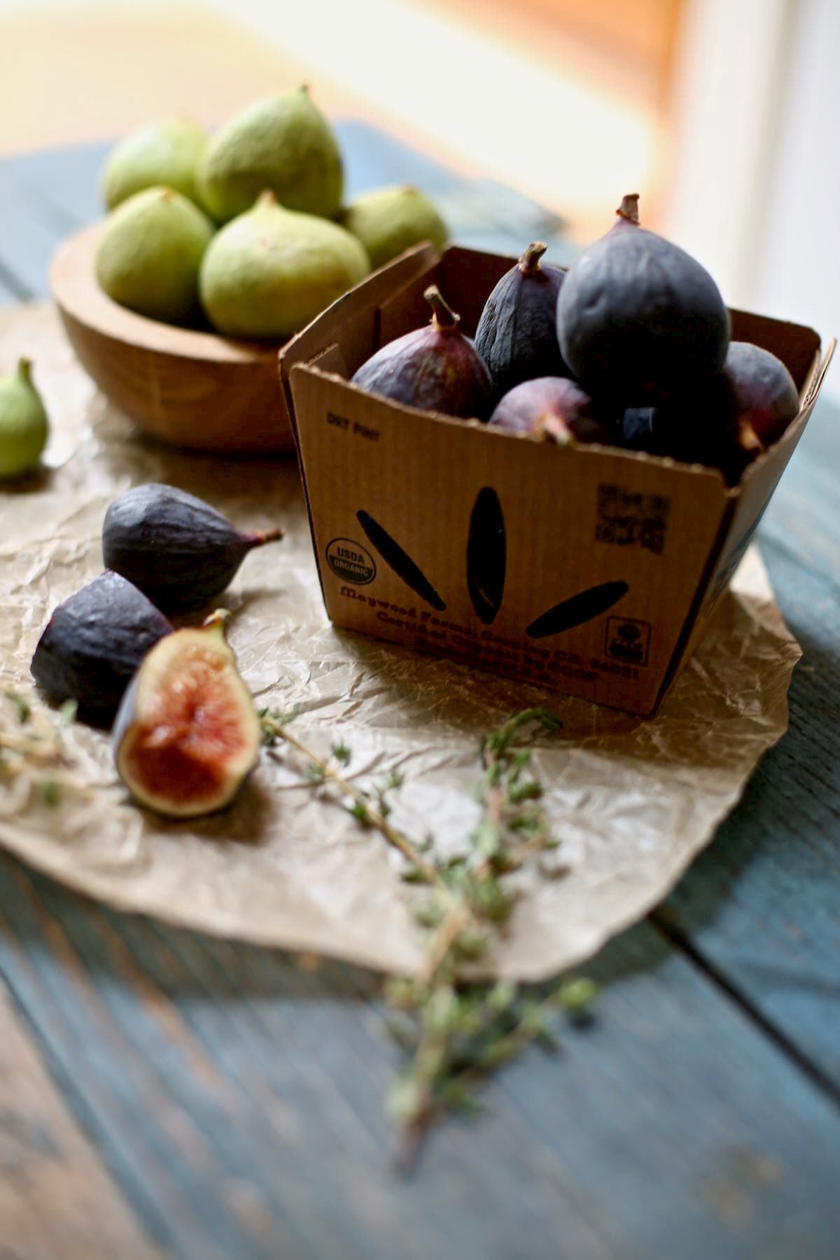 a basket of fresh figs on a blue table