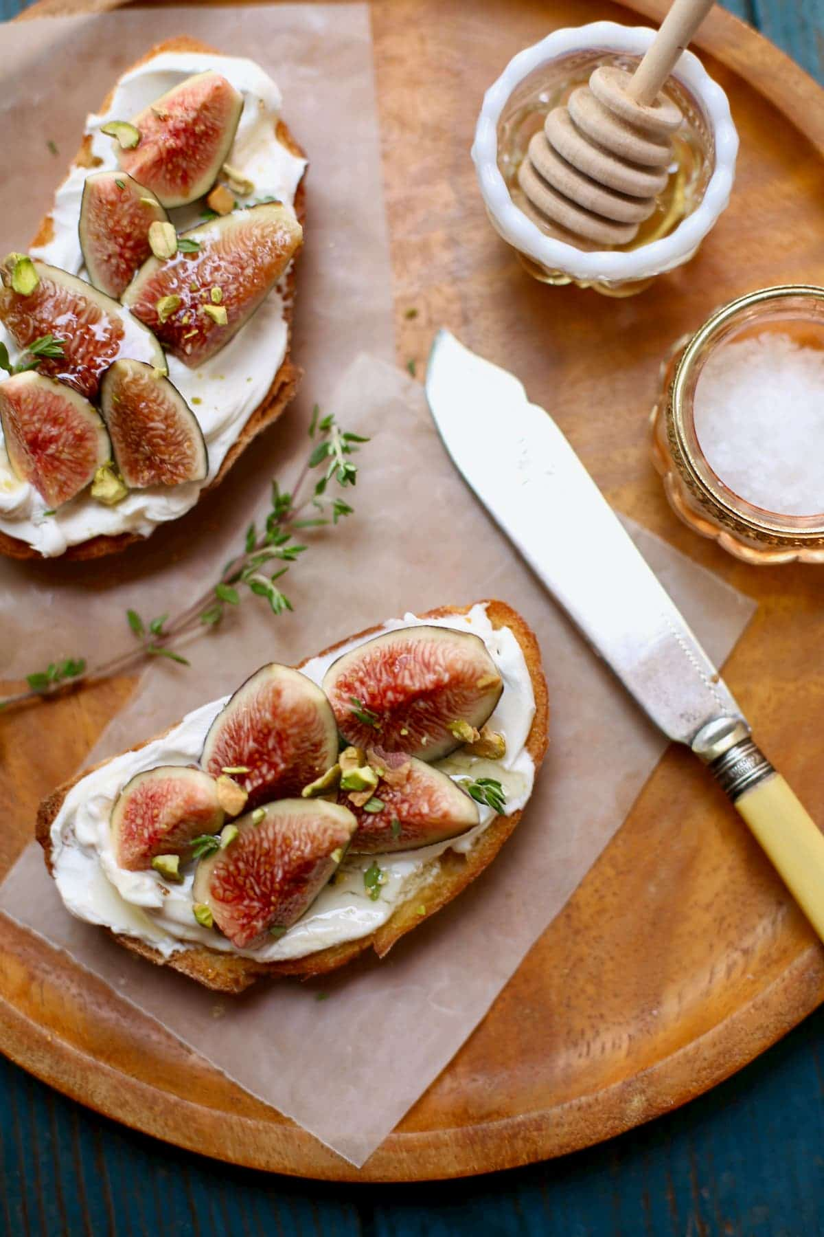 Fig toasts on a wooden plate with yellow knife and salt and honey