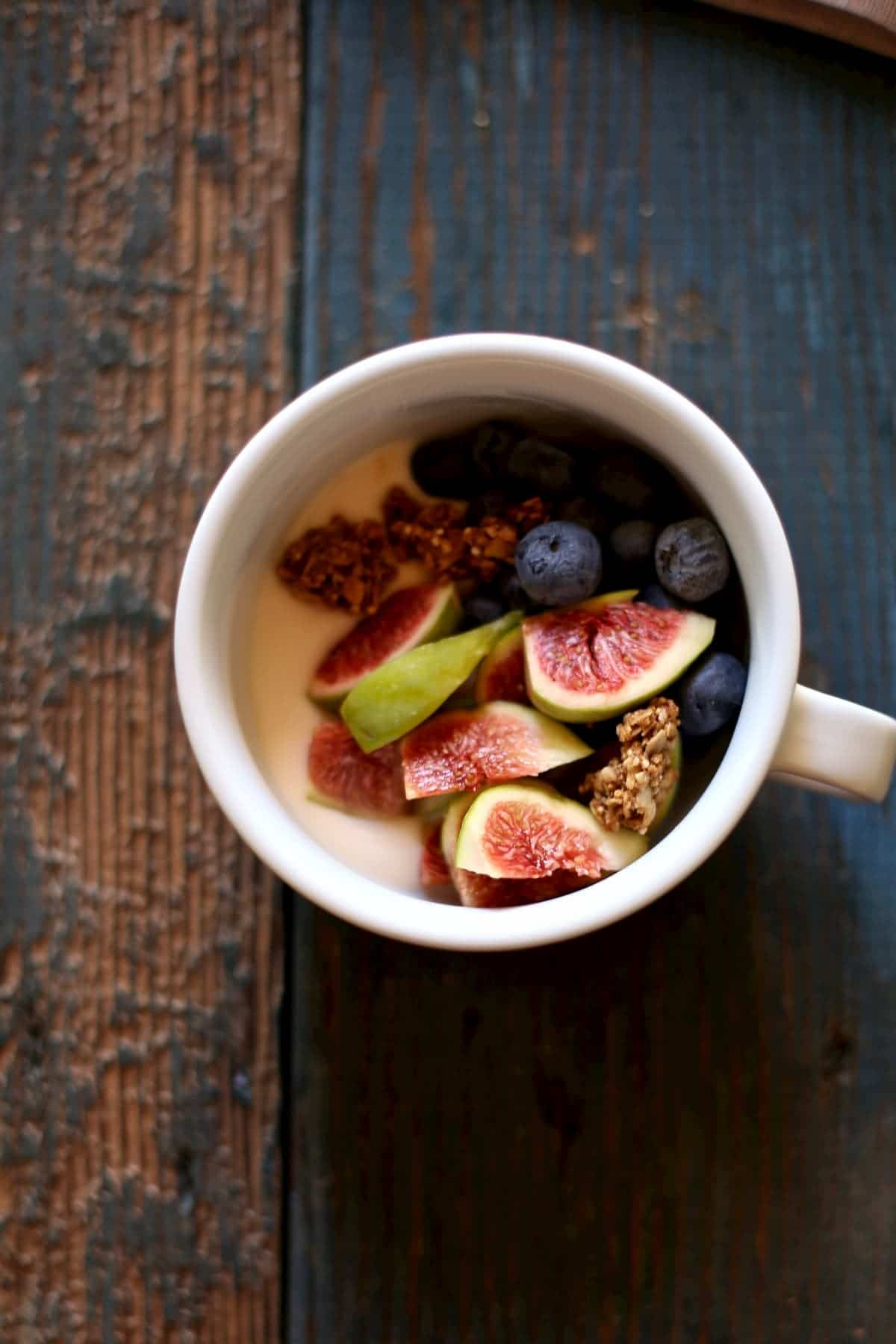 One bowl of yogurt and fresh figs on a wooden table