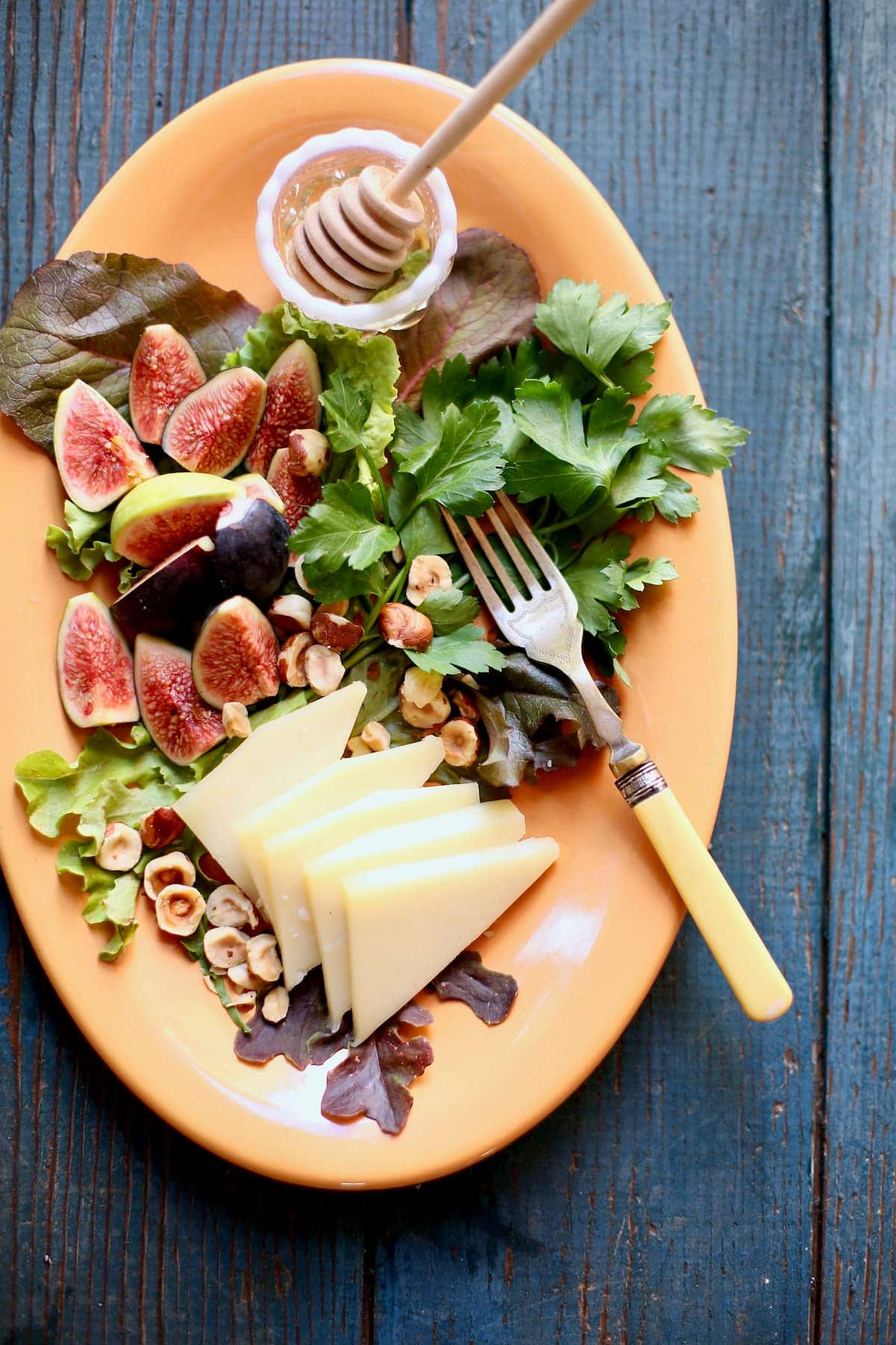 fig and cheese on an orange platter
