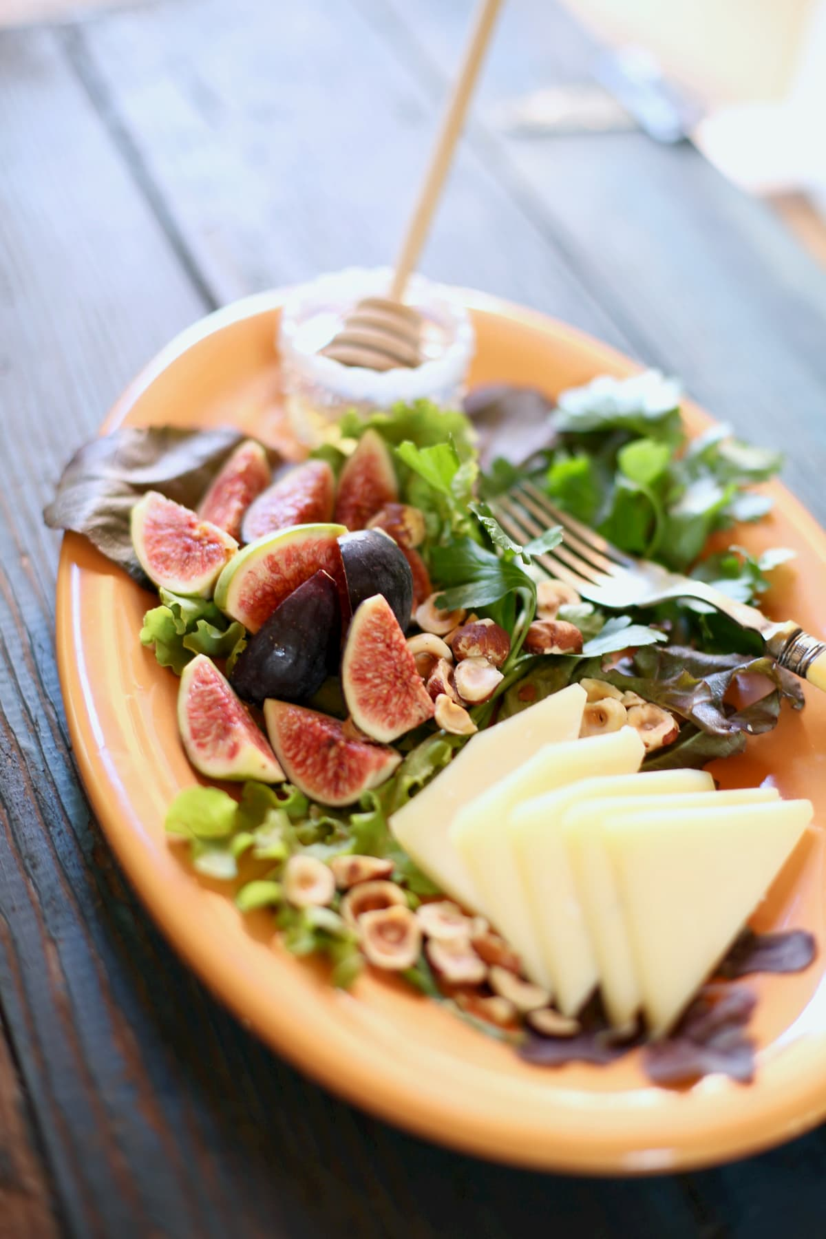 Figs, cheese and hazlenuts and honey on an orange platter