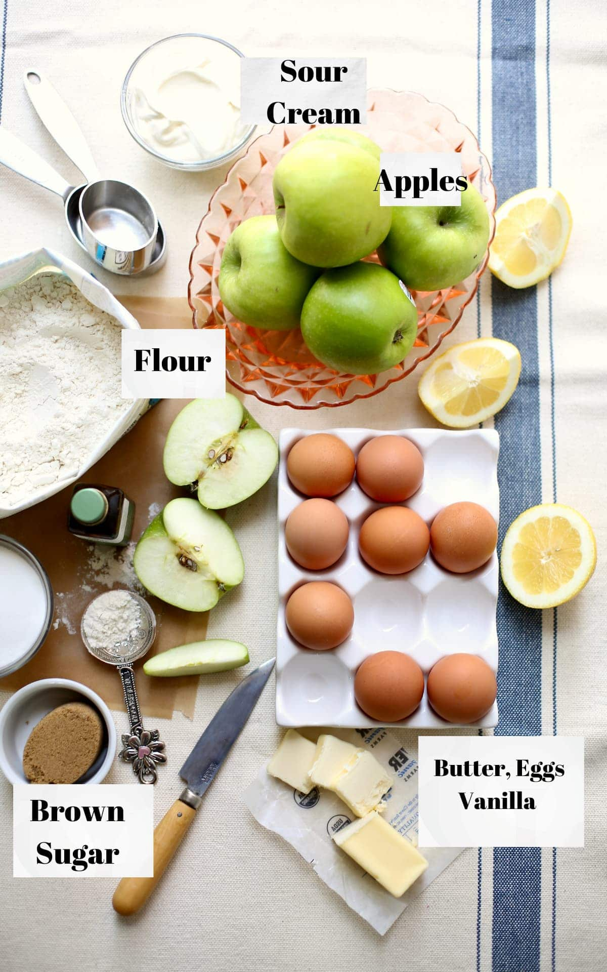 a photo of a table of ingredients for cake: apples, flour, eggs, butter, with a text overlay saying the names of the ingredients.