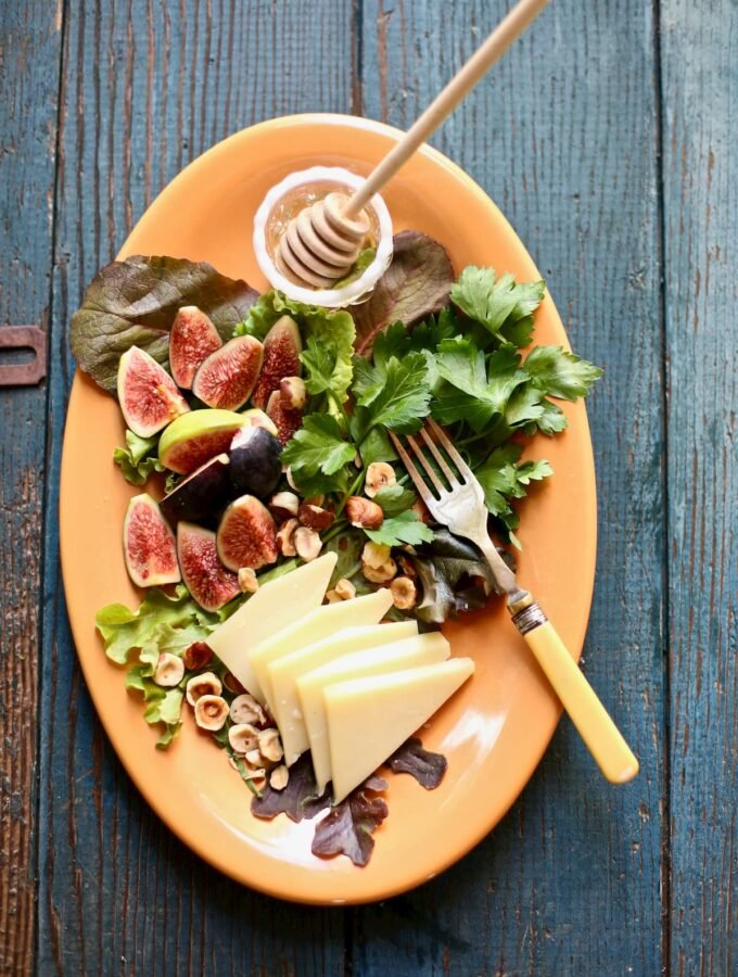 figs and greens and cheese and honey and a fork on a platter