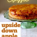 a cake on a green stand with text on top and to the side of it, saying the recipe name, upside down apple cake.