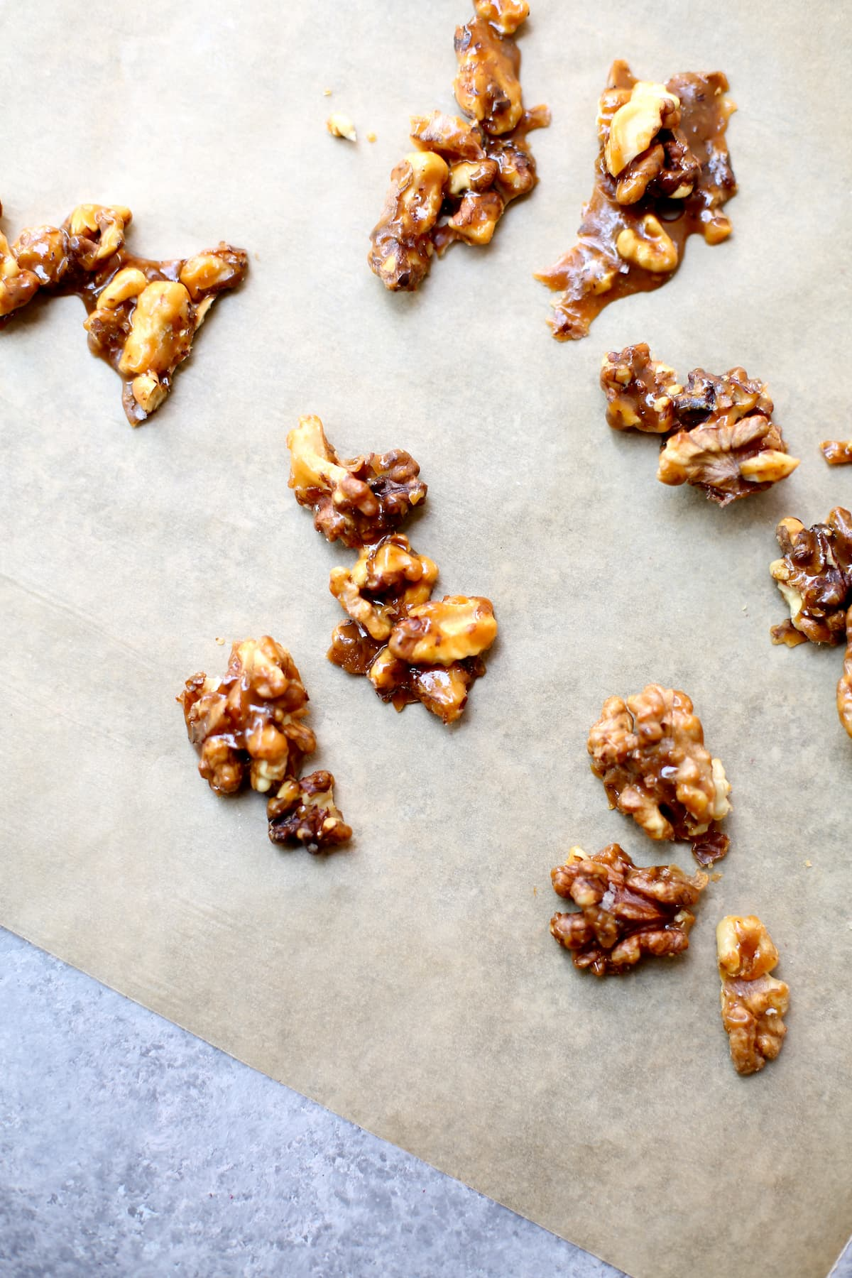 a baking tray lined with parchment paper with candied walnuts.