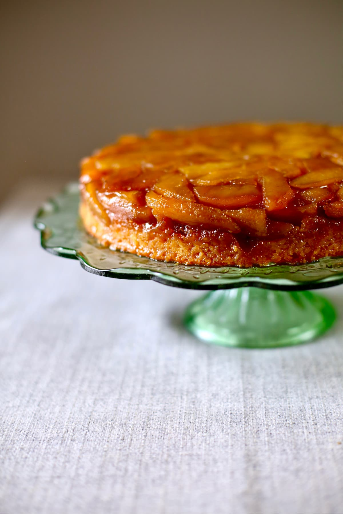 an apple cake on a green glass cake stand.