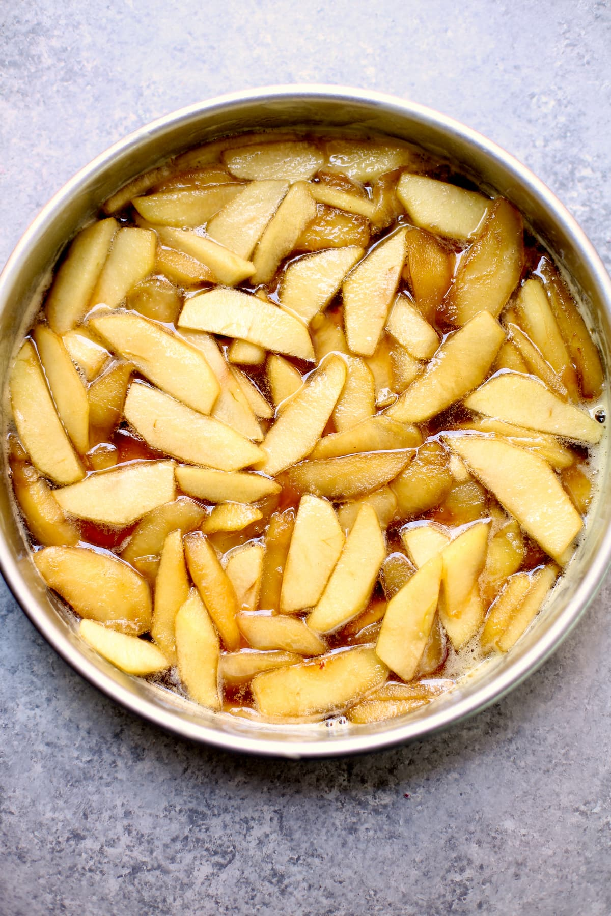 a round baking pan with raw sliced apples on a gray table.