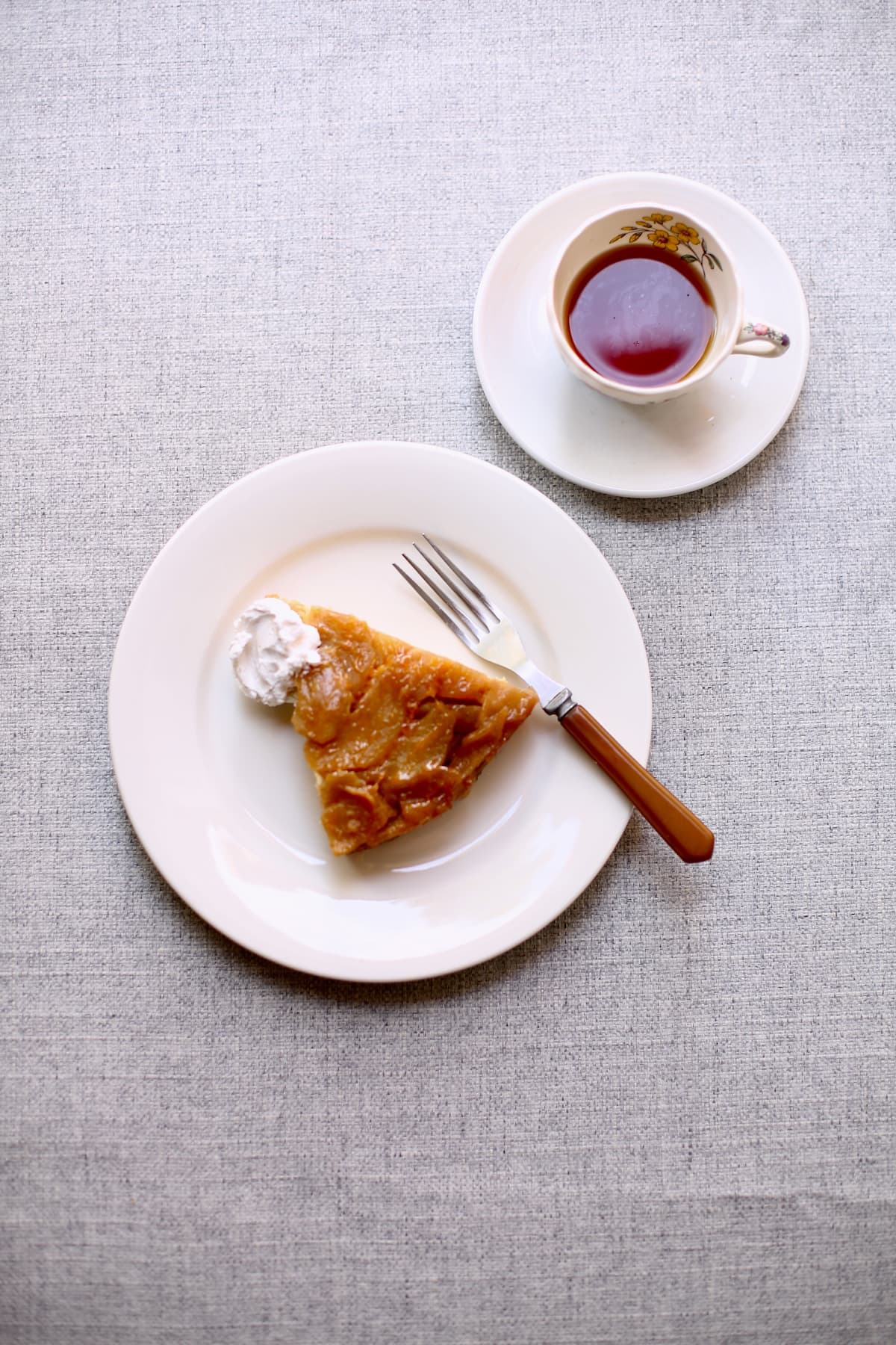 a piece of cake on a white plate, with a saucer of hto tea next to it. The plate has a brown fork next to it.
