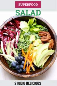 salad with blueberries pecans avacado and greens in a wooden bowl