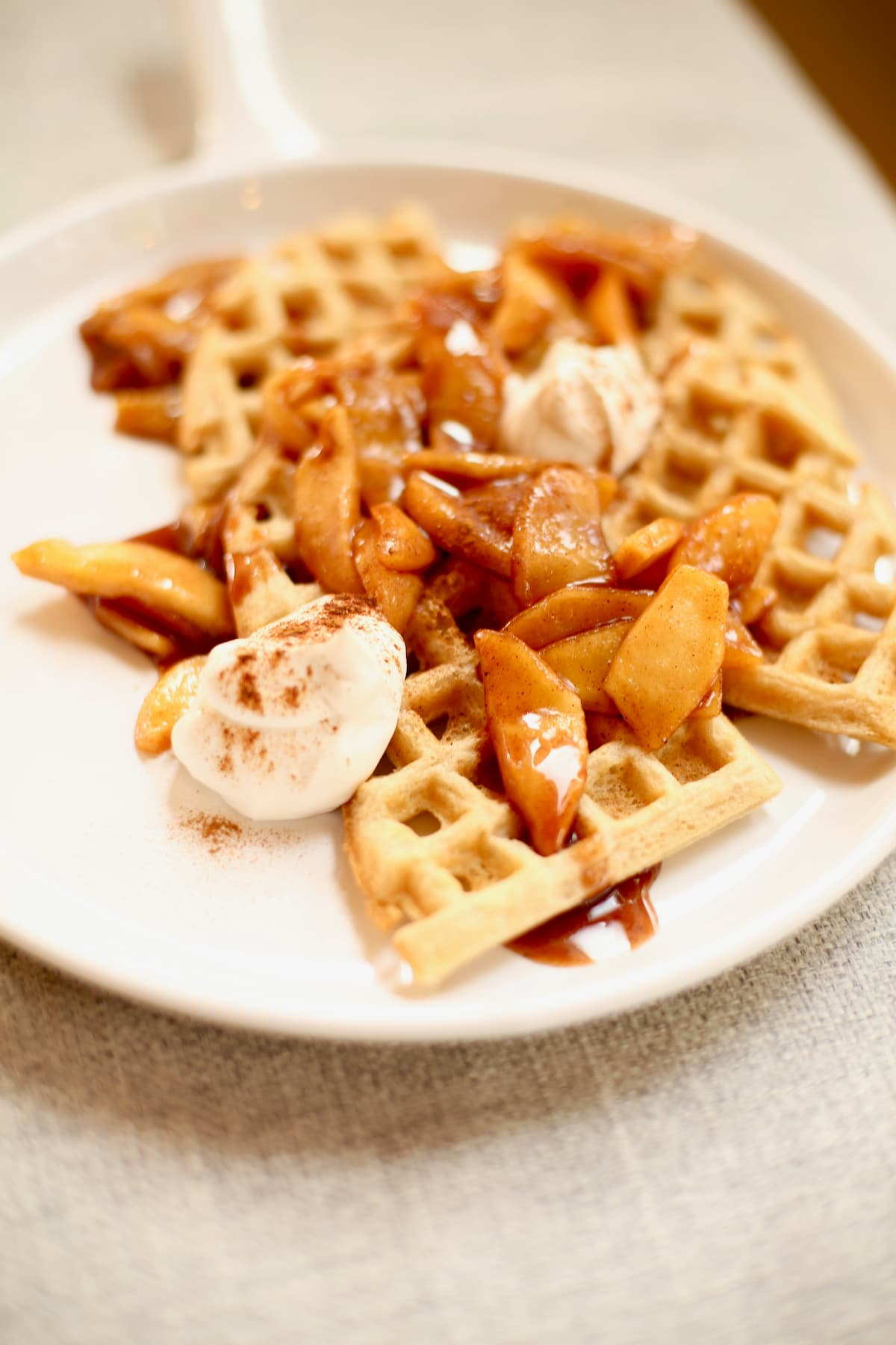waffles with apples on a white plate