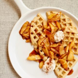 waffles and apples on a white platter with yogurt on top