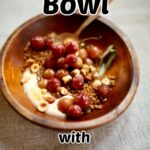 a wooden bowl of grapes and wheta berries and nuts and yogurt with a spoon