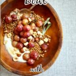 a big bowl of grapes, yogurt, nuts and sage and wheat berries on a gray tablecloth.