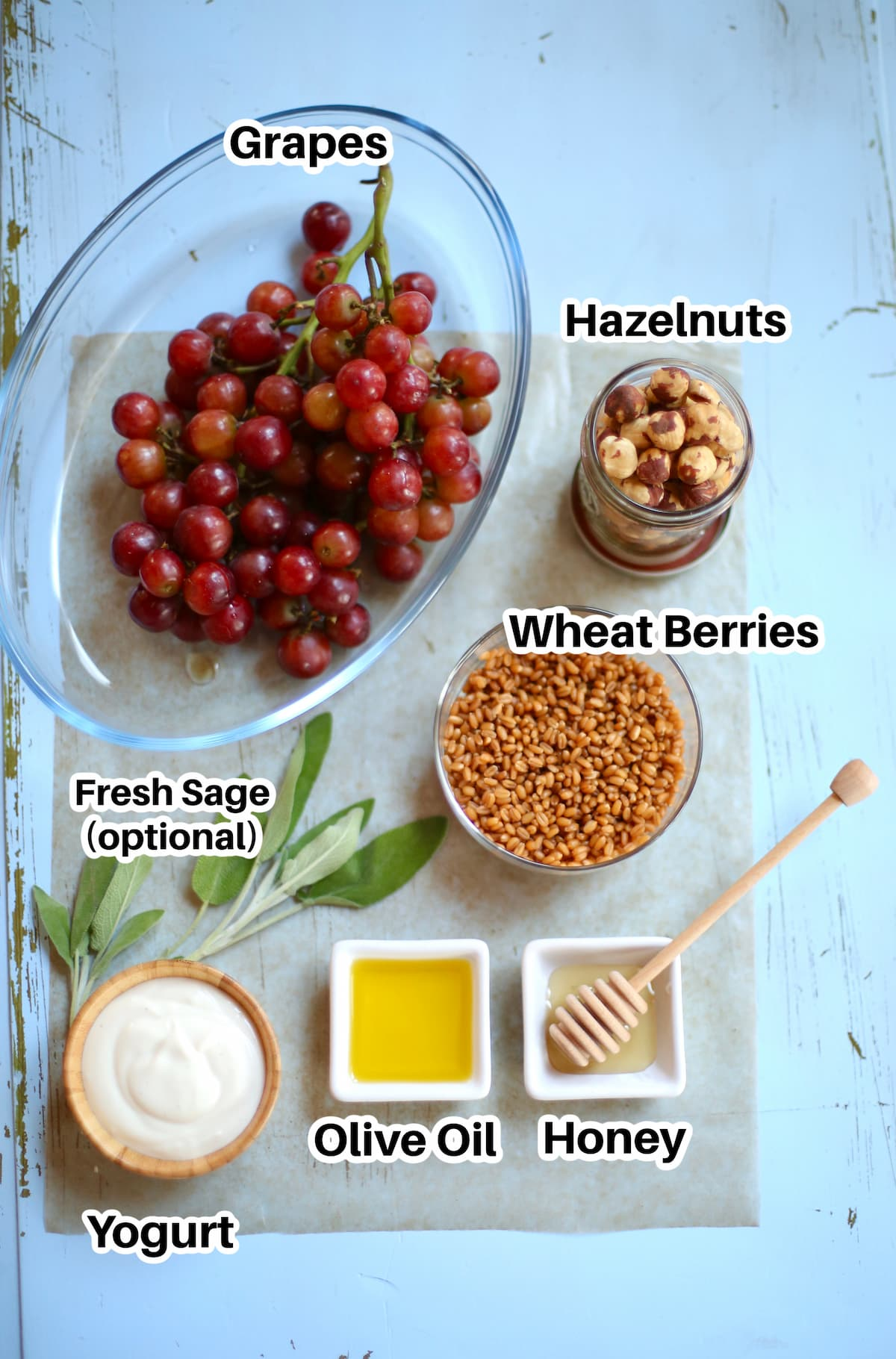 grapes, wheat berries, honey, olive oil and yogurt and hazelnuts on a blue table