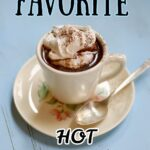 a white coffee mug of hot chocolate on a saucer with a spoon on a blue table with a text overlay saying the recipe name