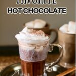 a glass mug of hot chocoalte on a tray with wooden spoon and text overlay saying the recipe name