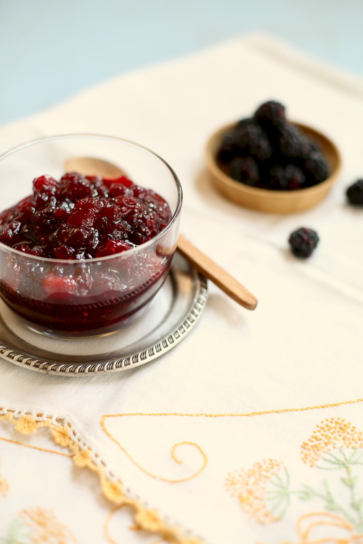 a glass bowl of cranberry sauce with blackberries behind it on a tablecloth with yellow trim.
