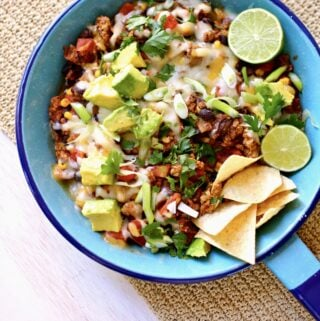 a blue skillet with cooked taco meat with melted cheese, chips, lime and avocado.