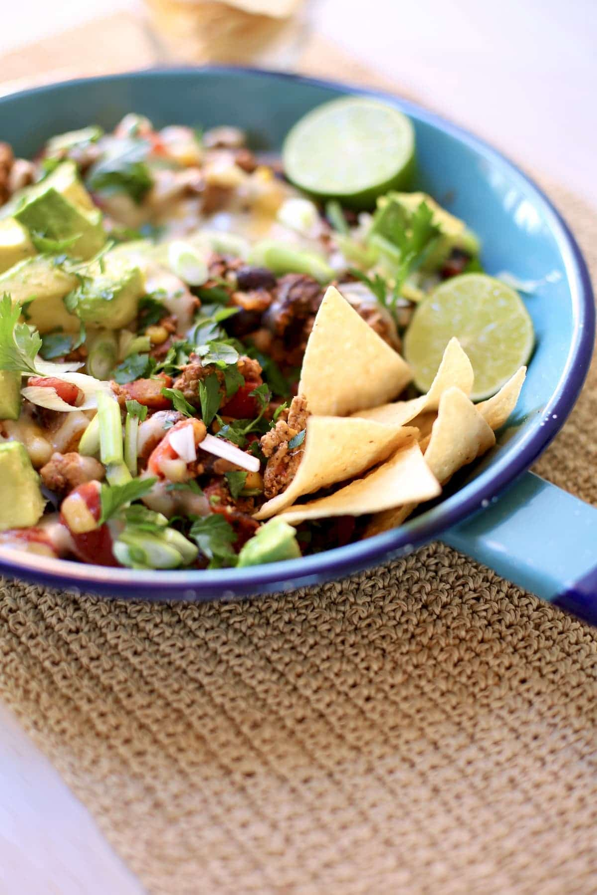 a blue skillet with taco meat, chips, lime and avocado