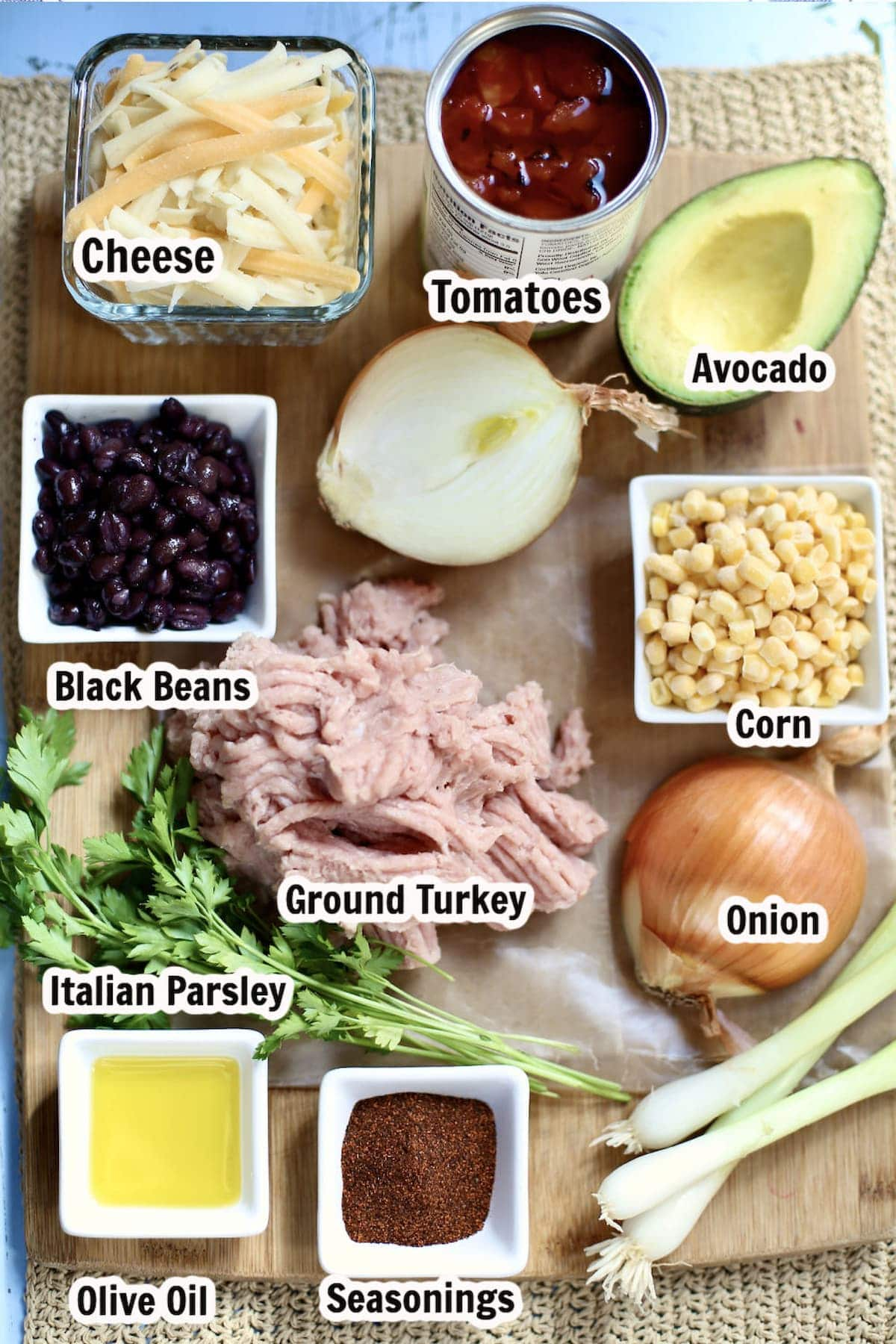 ingredients for a recipe marked with text overlay. Ground turkey, onion, black beans, cheese, avocado and corn.