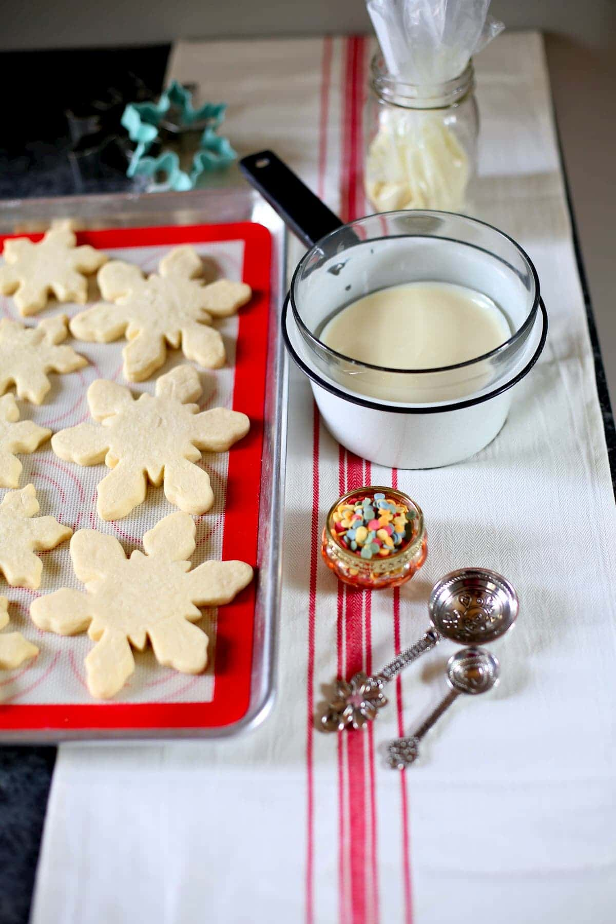 plain unfrosted snowflake cookies and melted white chocolate and sprinkles and measuring spoons on a table