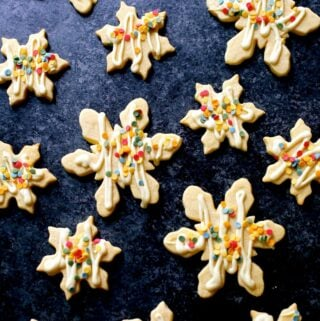 multiples of white chocolate snowflake cookies on a black board decorated