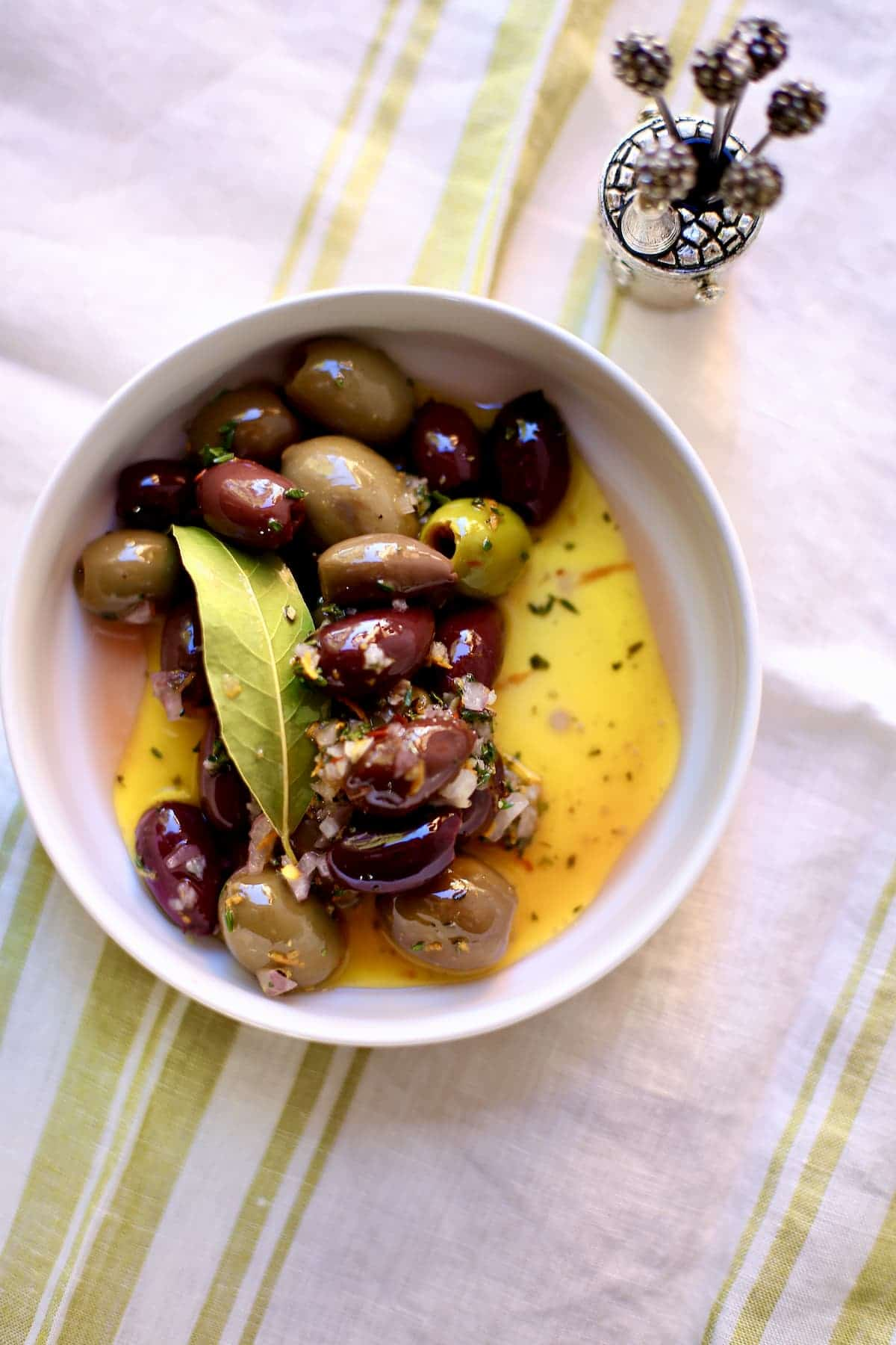 a bowl of colored olives with bay leaf and olive oil in a white bowl on a table