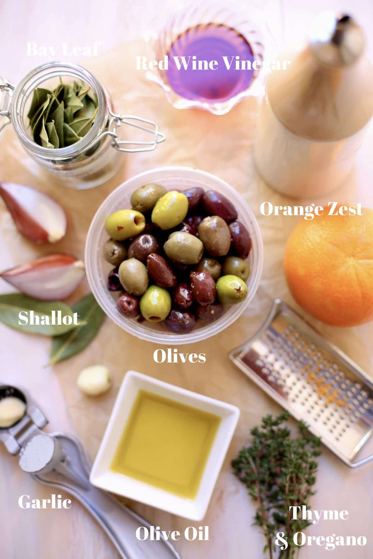 olives, orange, bay leaves, olive oil, shallot, thyme on on table with text underneath