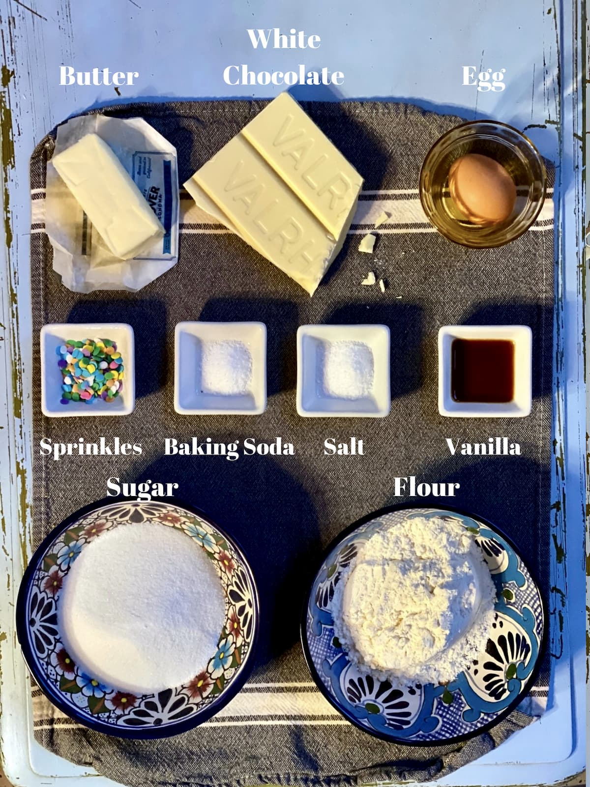 ingredients for white chocolate snowflake cookies, flour, butter, white chocolate, egg, baking powder, salt, vanilla and sprinkles