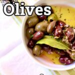 a bowl of party olives with bay leaf on a white tablecloth