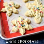 white chocolate snowflake cookies with white text on a baking sheet