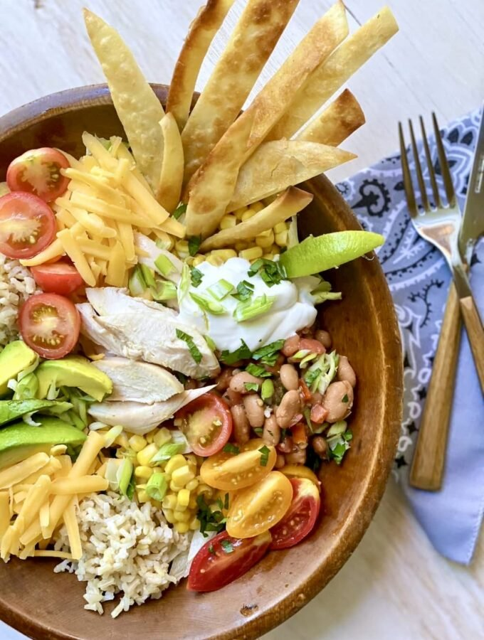 Closeup shot of a burrito bowl, tortillias, sour cream lime tomato cheese rice corn lettuce and a knife and fork