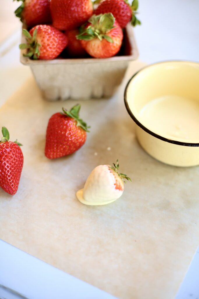 a set up of white chocolate and strawberries, one after being dunked and parchment paper