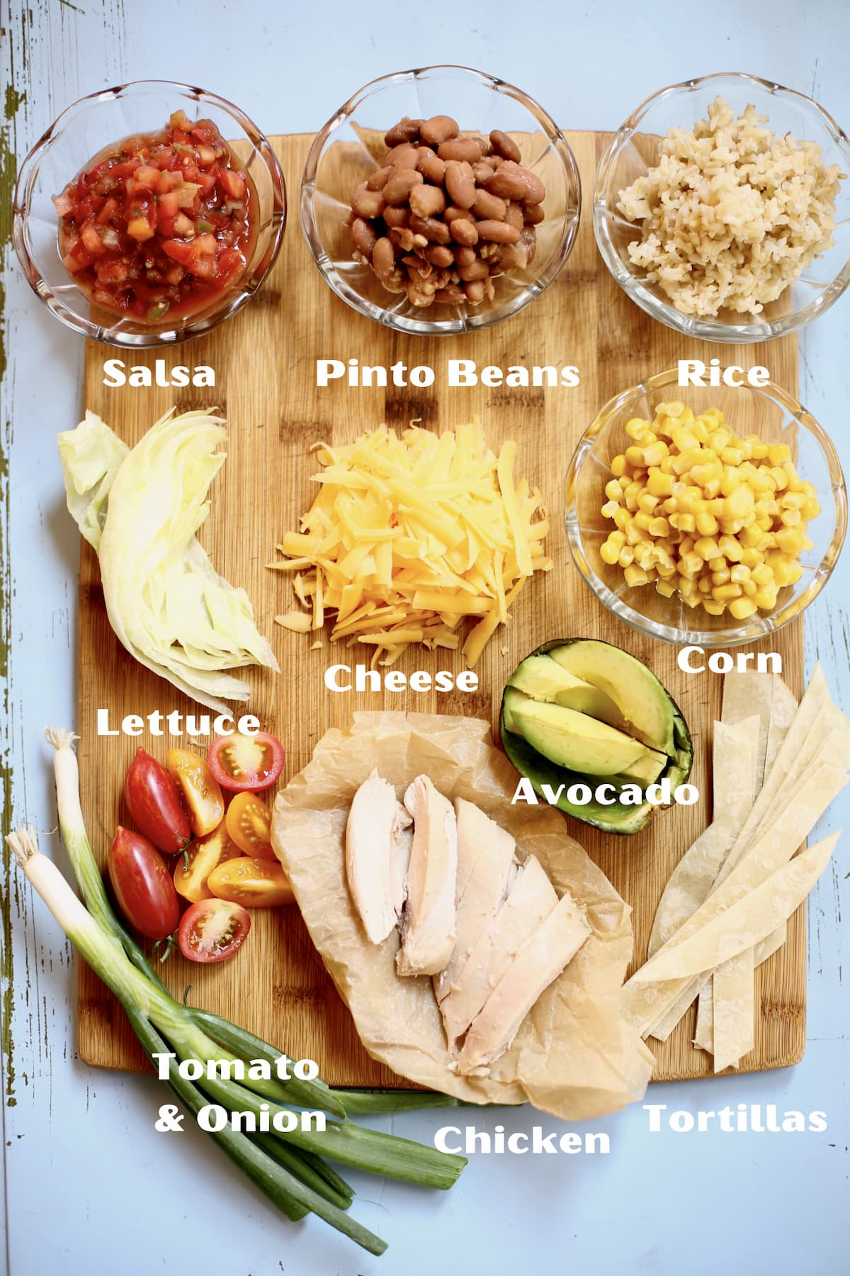 a cutting board of prepped ingredients for a meal,each one marked with text