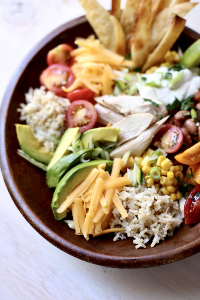 Close up photo of a bowl with cheese rice chicken tomatoes avaocado and corn