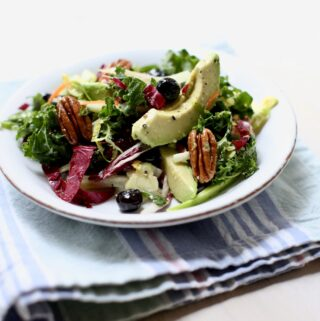 tossed green salad on a white plate on top of a striped cloth.