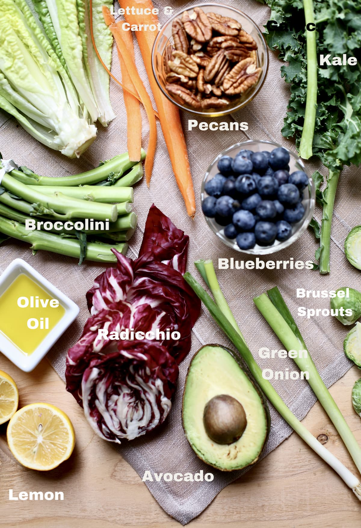 vegetables on a table with text overlay saying what they are: blueberries, brocolini, olive oil, avocado, green onion, pecans and more.