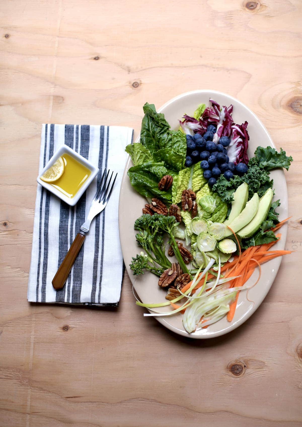 a large white platter of salad with a fork and lemon dressing alongside.